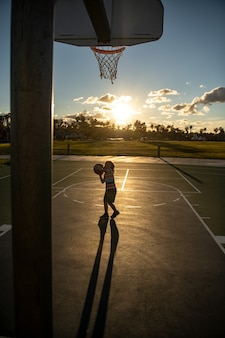 Treningowa gra w koszykówkę dla dzieci na sylwetce zachód słońca