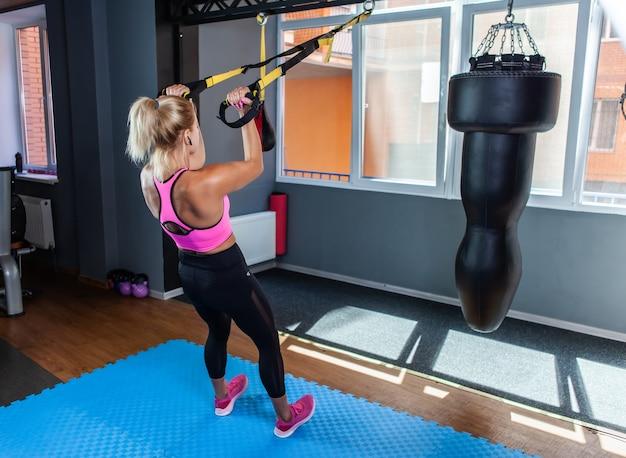 Treningowe pasy do zawieszania. sporty kobiety trenujące z pasami fitness trx na siłowni. piękna pani ćwicząca mięśnie w temblaku lub zawieszeniu na pasach.