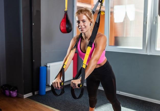 Treningowe pasy do zawieszania. uśmiechnięta sportowa kobieta trenująca z paskami trx w siłowni