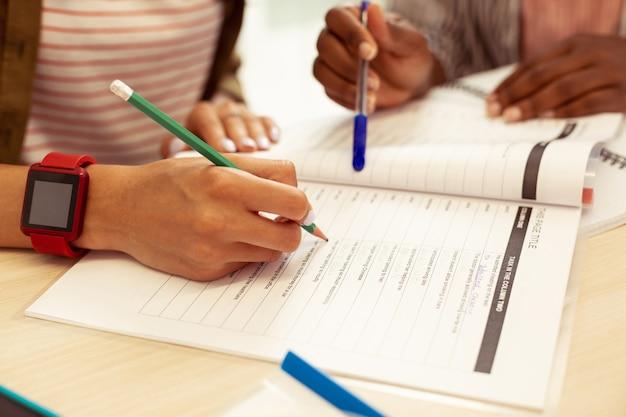 Trenuj gramatykę. zbliżenie kobiecej dłoni, która używa ołówka podczas robienia notatek