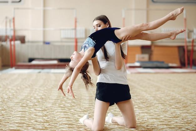 Trenuj z uczniem. dziewczęta gimnastyczki, wykonują różne ćwiczenia gimnastyczne i skoki. dzieci i sport, zdrowy tryb życia.