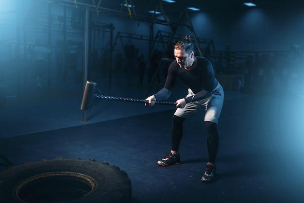Trenując na siłowni, mężczyzna z młotem uderza oponę. aktywne ćwiczenia w klubie sportowym
