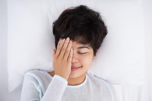 Treść kobieta obejmuje jedno oko i leży w łóżku
