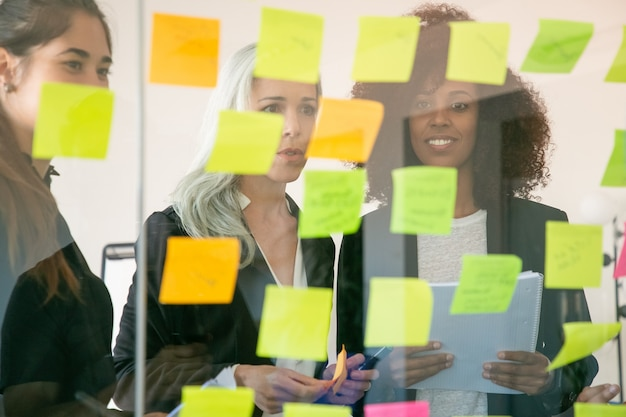 Treść młodych przedsiębiorców omawiających plan marketingowy i robienie notatek na naklejkach. udane, pewni siebie koledzy w garniturach spotykają się w biurze. koncepcja pracy zespołowej, biznesu i burzy mózgów
