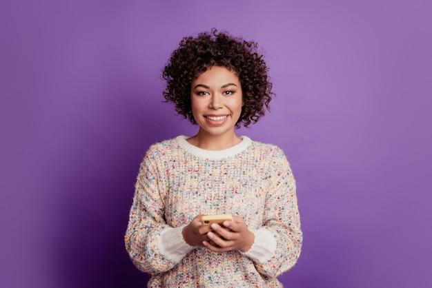 Treść modna wesoła ładna urocza urocza dziewczyna trzyma telefon ząbkowany promienny uśmiech na fioletowej ścianie
