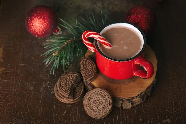 Treść świąteczna, czerwony kubek z kakao, lollipop, drewniany stojak, czekoladowe ciasteczka, gałązka świerkowa, choinka, czerwone kulki, ciemne tło
