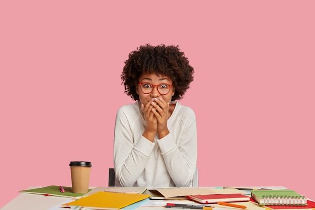 Treść zdziwiona czarnoskóra kobieta zakrywa usta, wygląda radośnie, nie wierzy w promocję, ma zadowoloną reakcję na coś pozytywnego, siedzi stacjonarnie przy pulpicie. uradowany student studiuje w domu