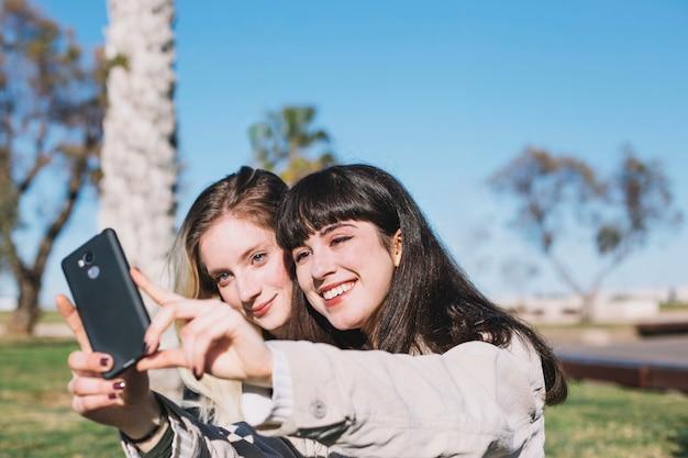 Treściowe jaskrawe dziewczyny pozuje dla selfie
