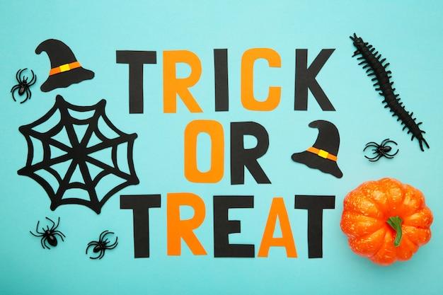 Trick or treat napis z dekoracją halloweenową na niebieskiej pastelowej powierzchni