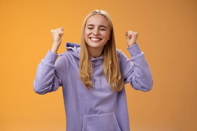 Triumfując świętując pozytywną jasnowłosą młodą zwyciężczynię podnieś ręce zaciśnij pięści w górę gest zwycięstwa zamknij oczy szeroko uśmiechnięte, chętnie przyjmując wspaniałą ofertę, osiągaj sukces.