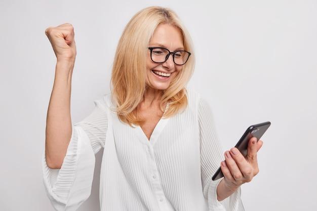 Triumfująca pozytywna blondynka w średnim wieku, zaciska pięść z radości, świętuje sukces, czyta niesamowite wiadomości przez smartfona, otrzymuje pozytywne opinie, nosi okulary i bluzkę na białej ścianie