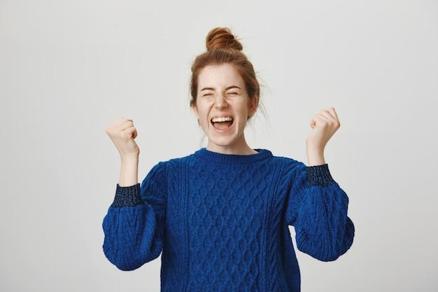Triumfująca śliczna ruda dziewczyna świętuje osiągnięcie, krzycząc tak