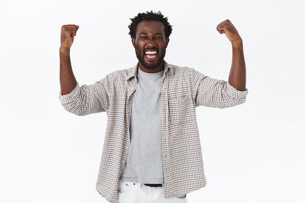 Triumfujący szczęśliwy afro-amerykański brodaty facet czujący się jak mistrz