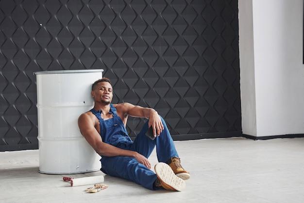 Trochę czasu na odpoczynek. afroamerykanin siedzi na podłodze i pochylony do białej beczki