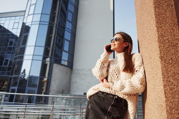Trochę dobrych wiadomości. młoda piękna dziewczyna w ciepłych ubraniach spaceruje po mieście w weekendy