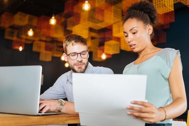 Trochę księgowości. para młodych zamożnych biznesmenów robi pewne rachunkowości podczas ciężkiej pracy