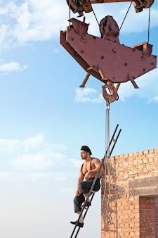 Trochę odpoczywam. przystojny budowniczy bez koszuli siedzący na drabinie w budowanym wieżowcu