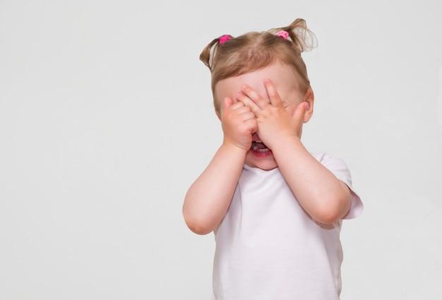 Trochę przestraszona, płacząca lub bawiąca się dziewczyna ukrywa twarz