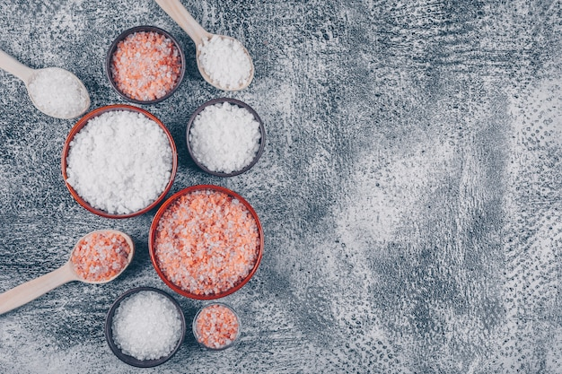 Trochę soli morskiej z himalajską solą w szklance, misach i drewnianych łyżkach