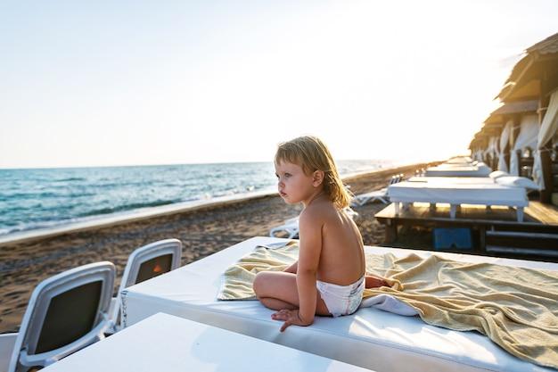 Trochę szczęśliwa dziewczyna na morzu w bungalowie vip siedzi z widokiem na morze o zachodzie słońca
