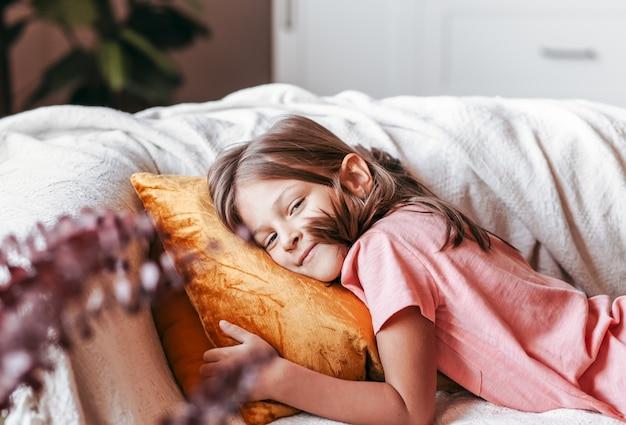 Trochę uśmiechnięta dziewczyna leży na kanapie. szczęśliwe dzieciństwo. odpoczynek dla dzieci