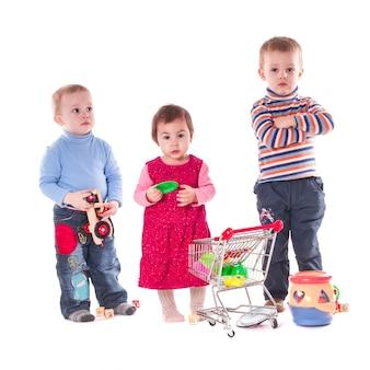 Troje dzieci bawi się zabawkami na białym tle