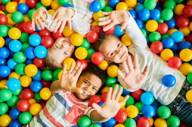 Troje dzieci bawiące się w ballpit