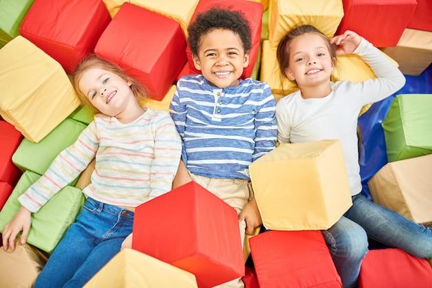 Troje dzieci bawiących się w piankowym pianie