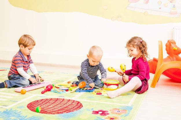 Troje dzieci bawiących się w pokoju zabaw. dzieci fantazjują, że są muzykami. dziewczyna gra na perkusji, pierwszy chłopak gra na ksylofonie, drugi na pianinie.