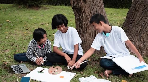 Troje dzieci siedzących na parterze na zielonej trawie, malujących na płótnie i rozmawiających, wspólnie wykonujących zabawę w parku