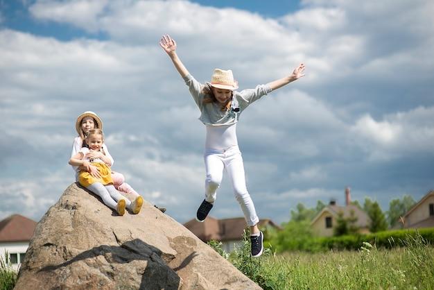 Troje dzieci siedzi grając, skacząc na dużym kamieniu na świeżym powietrzu