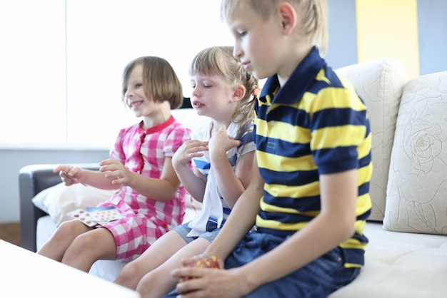 Troje dzieci siedzi na sofie w pokoju. chłopiec trzyma talię kart w rękach