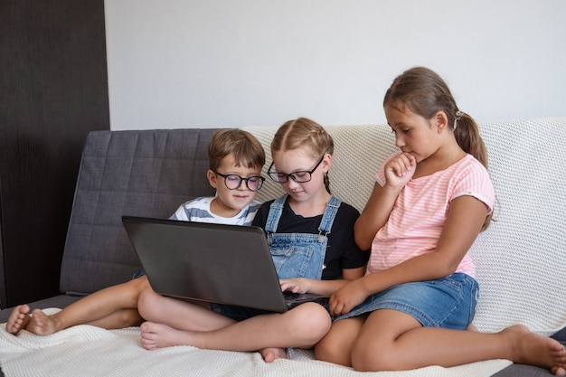 Troje dzieci w okularach za pomocą laptopa i telefonu podczas nauki w domu. powrót do koncepcji szkoły.
