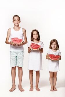 Troje dzieci w pracowni stoi na białym tle i trzyma kawałki arbuza brat dwie siostry boso w jasnych ubraniach szczęśliwe dzieciństwo prawidłowe zasilanie