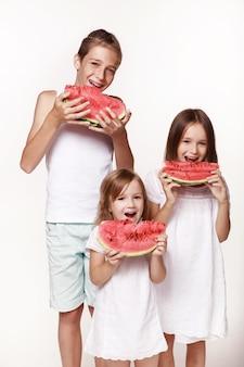 Troje dzieci w studiu stoi na białym tle i je kawałki arbuza i śmieje się brat dwie siostry w jasnych ubraniach boso radosne dzieciństwo rozpieszczanie prawidłowe zasilanie