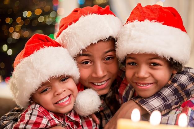 Troje dzieci w świątecznych kapeluszach. uśmiechnięci chłopcy afro na boże narodzenie. trzech szczęśliwych braci na wakacjach. wieczór wigilijny w rodzinnym domu.