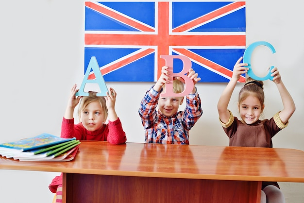 Troje małych dzieci na lekcji angielskiego