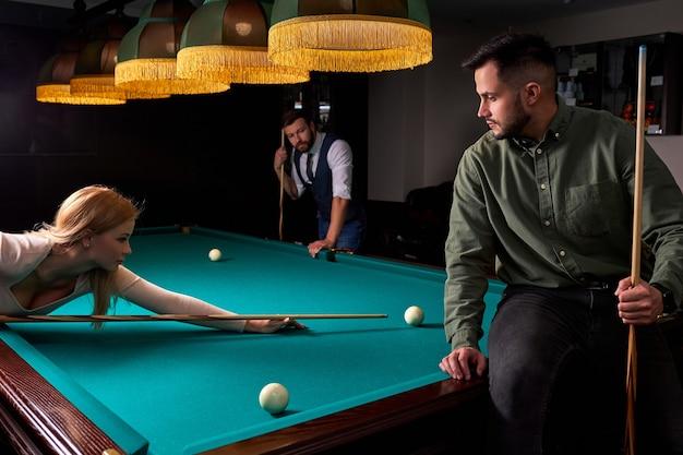 Troje przyjaciół grających razem w bilard, snookera lub bilard, cieszy się wolnym czasem. zabawa, bilard, wypoczynek, koncepcja odpoczynku