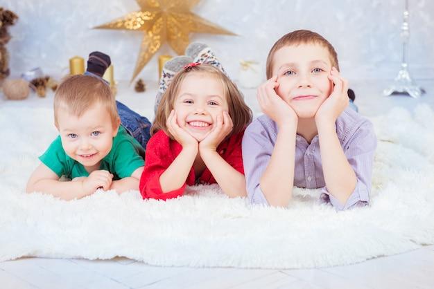 Troje roześmianych dzieci leży na białym dywanie w oczekiwaniu na wizerunek świętego mikołaja