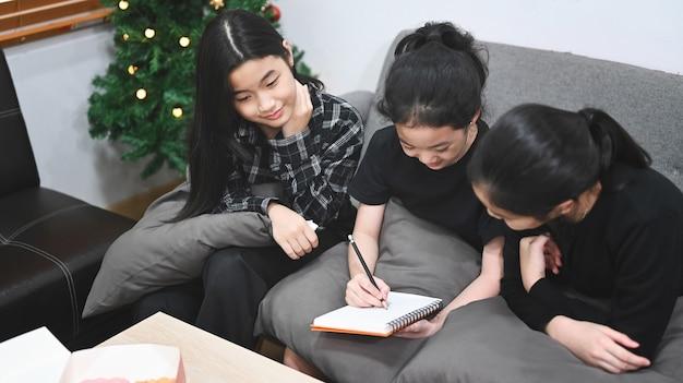 Troje szczęśliwych dzieci uczących się razem online w domu.