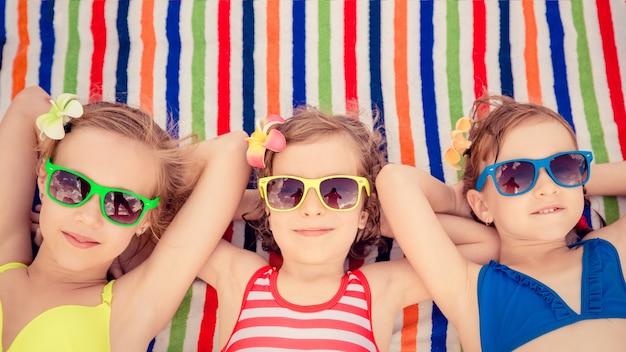 Troje szczęśliwych dzieci w kolorowych okularach przeciwsłonecznych leżących na kolorowym ręczniku plażowym w paski