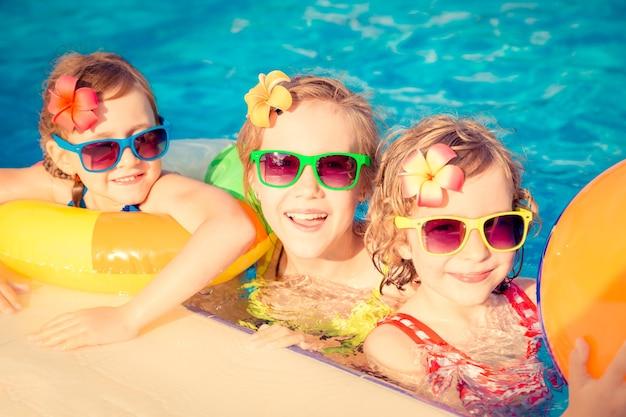 Troje szczęśliwych dzieci z kolorowymi okularami przeciwsłonecznymi i dmuchańcami na basenie
