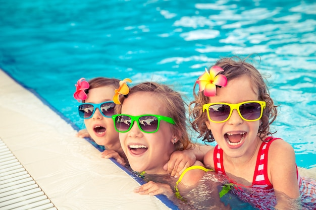 Troje szczęśliwych dzieci z kolorowymi okularami przeciwsłonecznymi na basenie