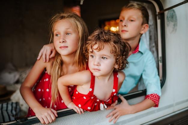 Troje uroczych dzieciaków wyglądających przez okno samochodu kempingowego