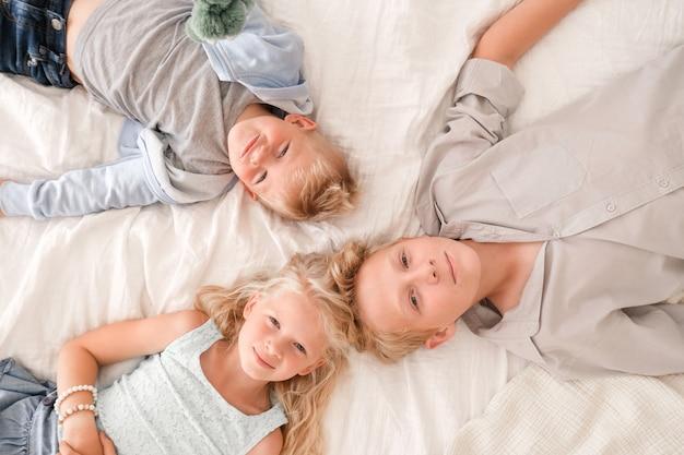 Troje wesołych blondynek leżą na łóżku, patrzą w kamerę i uśmiechają się. dwóch chłopców i dziewczynka.