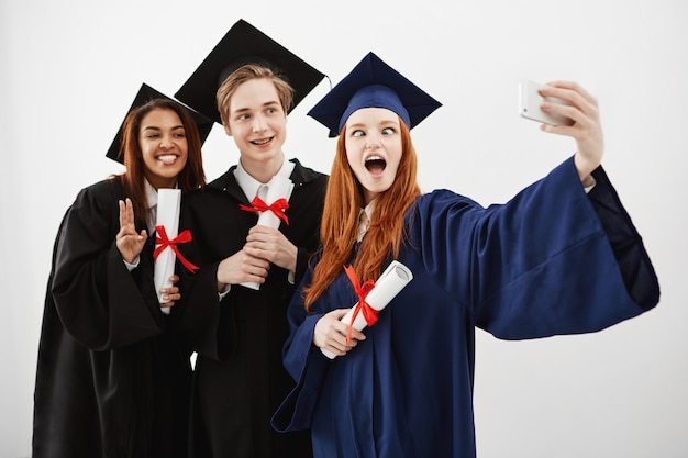 Troje wesołych szczęśliwych absolwentów wygłupiać się z zabawy uśmiechając się robiąc selfie z dyplomami w rękach, przyszłych prawników.