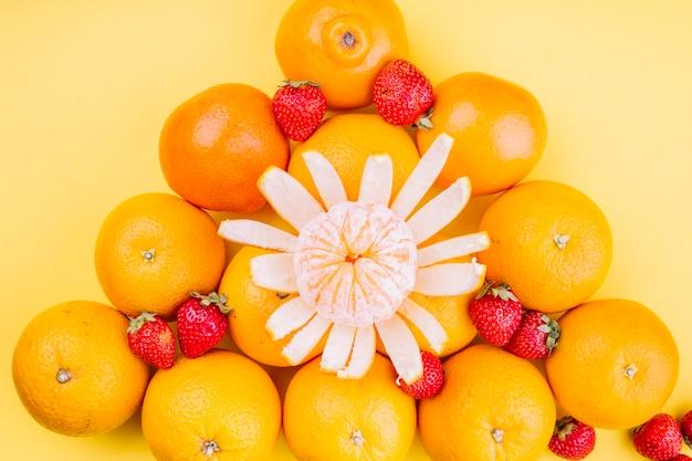 Trójgraniaste pomarańcze z truskawkami na żółtym tle