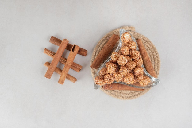 Trójkątna misa w towarzystwie kawałków cynamonu na trójnogu na marmurowym stole.