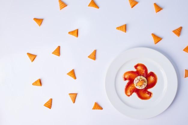 Trójkątne chipsy ziemniaczane podawane z czerwonym sosem pomidorowym.