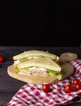Trójkątne kanapki z grzanką, sałatą i warzywami na ciemnym tle. zdrowe i pyszne śniadanie lub obiad.